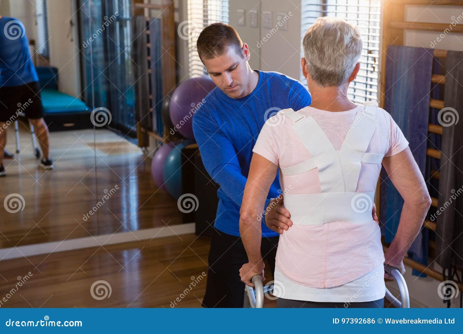Fisioterapeuta que ajuda ao paciente a andar com quadro de passeio