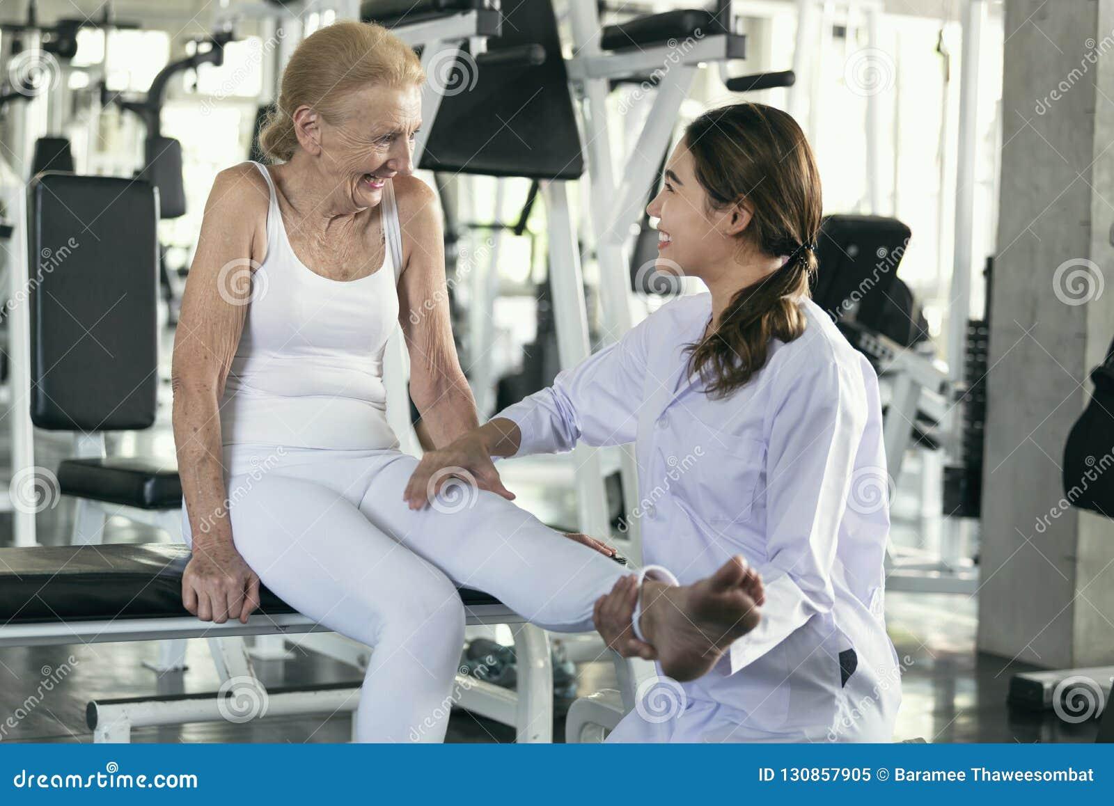 Fisioterapeuta que ajuda a mulher superior idosa no centro físico conceito idoso do estilo de vida da saúde