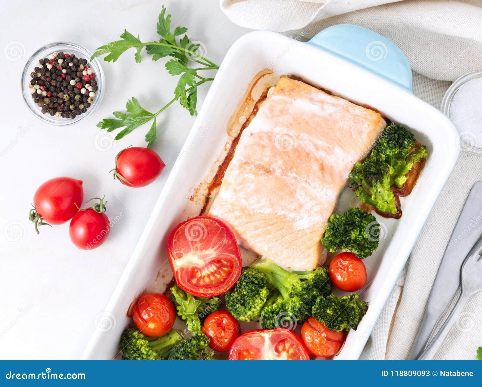 Fiska laxen som bakas i ugn med grönsaker, broccoli Sunt banta mat, den vita marmorbakgrunden, den bästa sikten, närbild