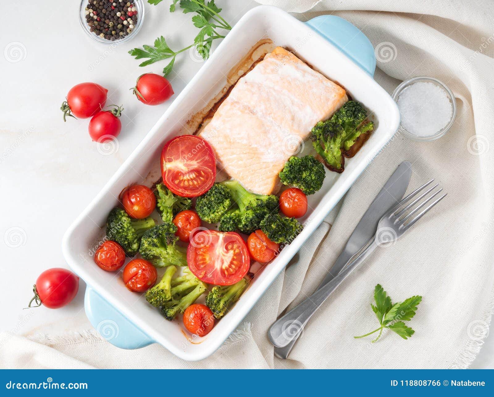 Fiska laxen som bakas i ugn med grönsaker - broccoli, tomater Sunt banta mat, den vita marmorbakgrunden, bästa sikt