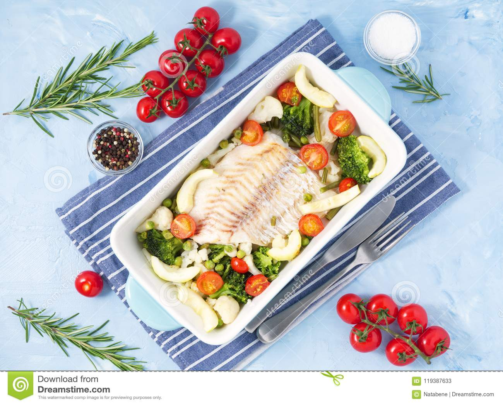 Fiska torsk som bakas i blå ugn med grönsaker - broccoli, tomater banta sund mat Bakgrund för blå sten, bästa sikt