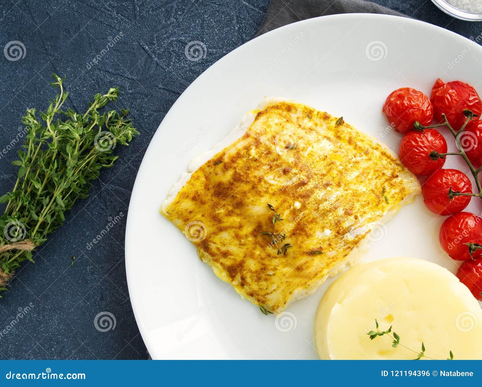 Fiska torsk som bakas i ugn med mosade potatisar, tomater, banta sund mat Mörker - grå bakgrund, bästa sikt