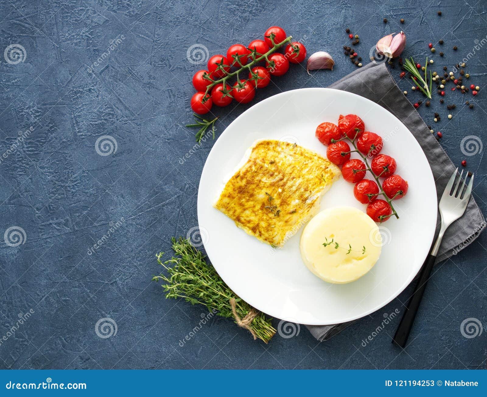 Fiska torsk som bakas i ugn med mosade potatisar, tomater, banta sund mat Mörker - grå bakgrund, bästa sikt, kopieringsutrymme
