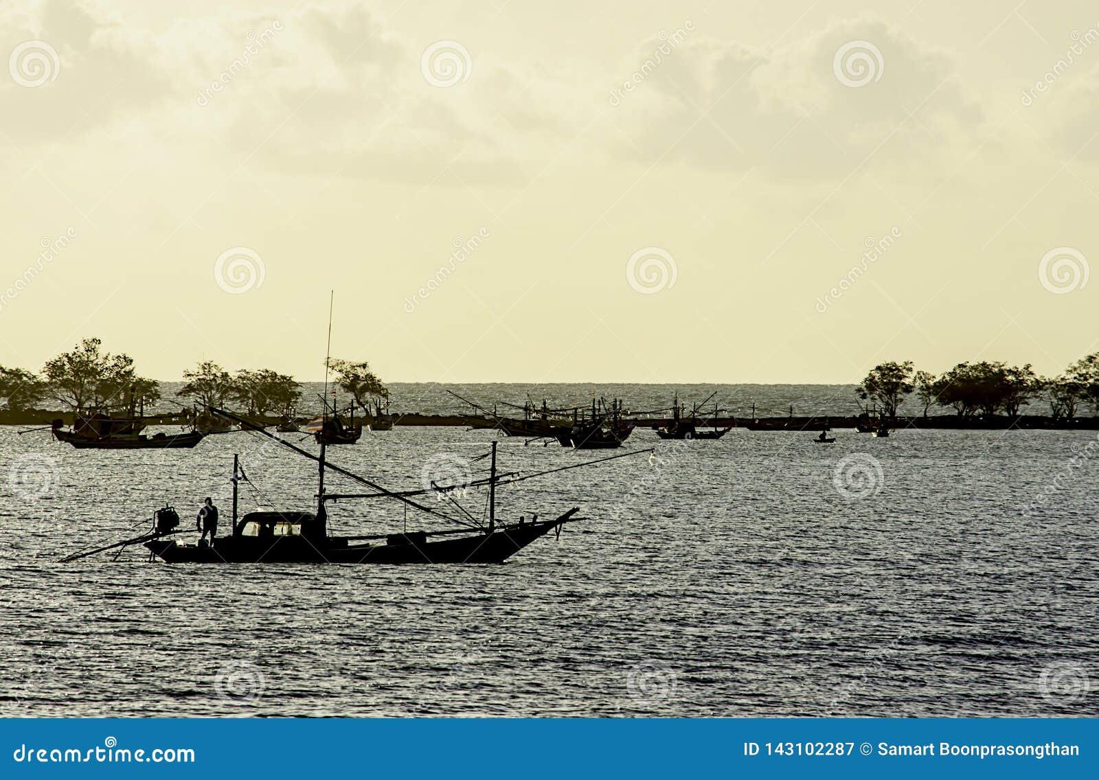 Fiskare på fartyget och fiskebåtarna som parkeras på havskustlinjen på Laem den thian stranden, Chumphon i Thailand