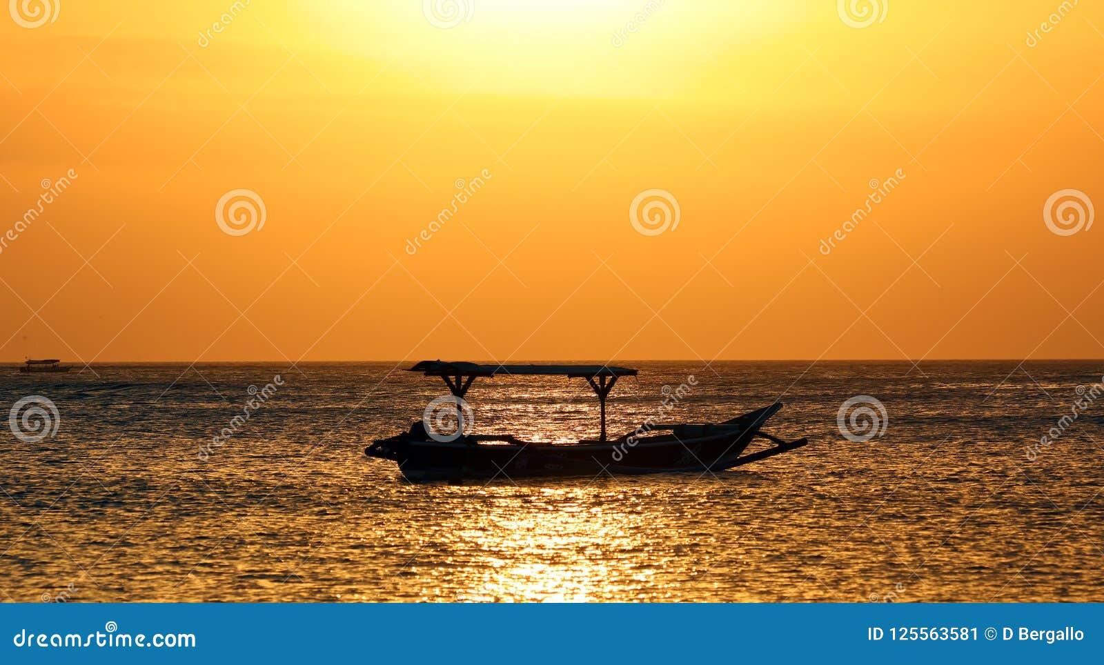 Fiskarefartyg i Bali, Indonesien under guld- solnedgång Hav och himmel som ser som guld