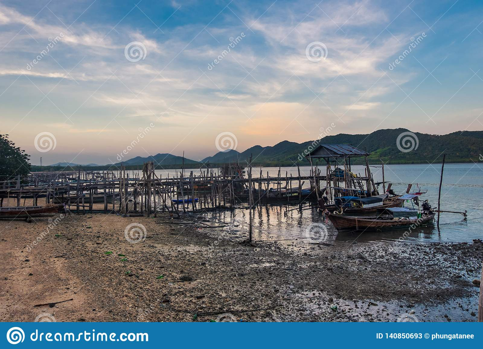 Fiskebåtar som parkeras på pir i en fiskareby med härliga berg och himmel bakom, hav södra Thailand, Phang Nga, Koh