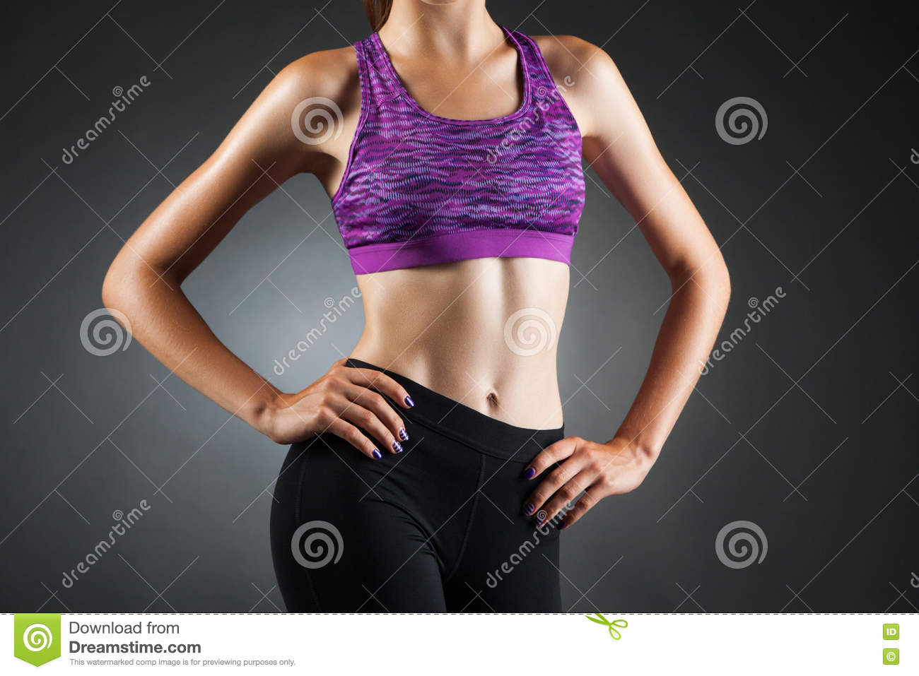 6bf768a1b Fit anonymous sport-girl akimbo in black yoga pants and purple top. Studio  portrait black background.