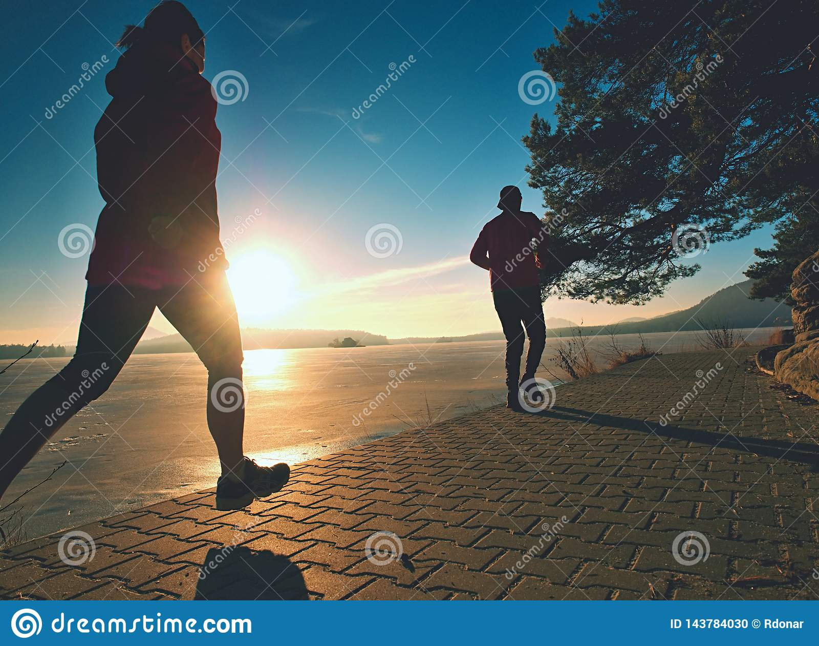 Fit couple, man and woman running along waterfront