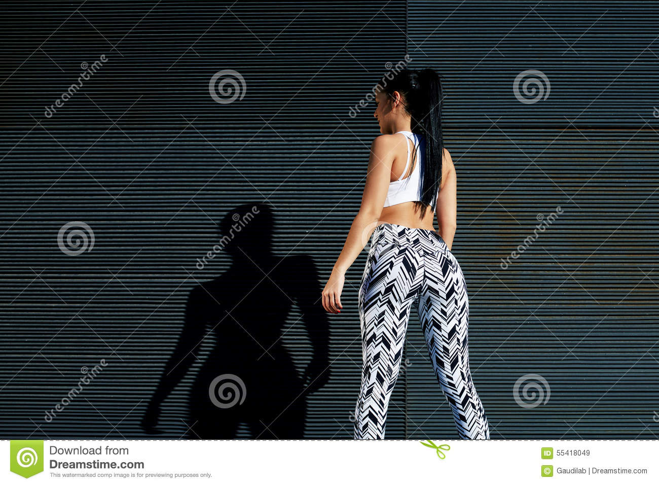 fit female in sportswear resting after training on black background outdoors