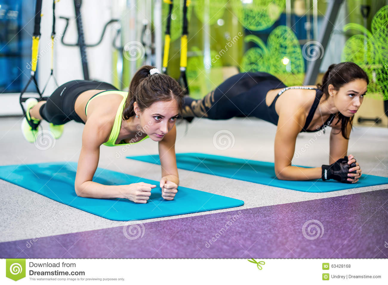 Fit girls in gym doing plank exercise for back