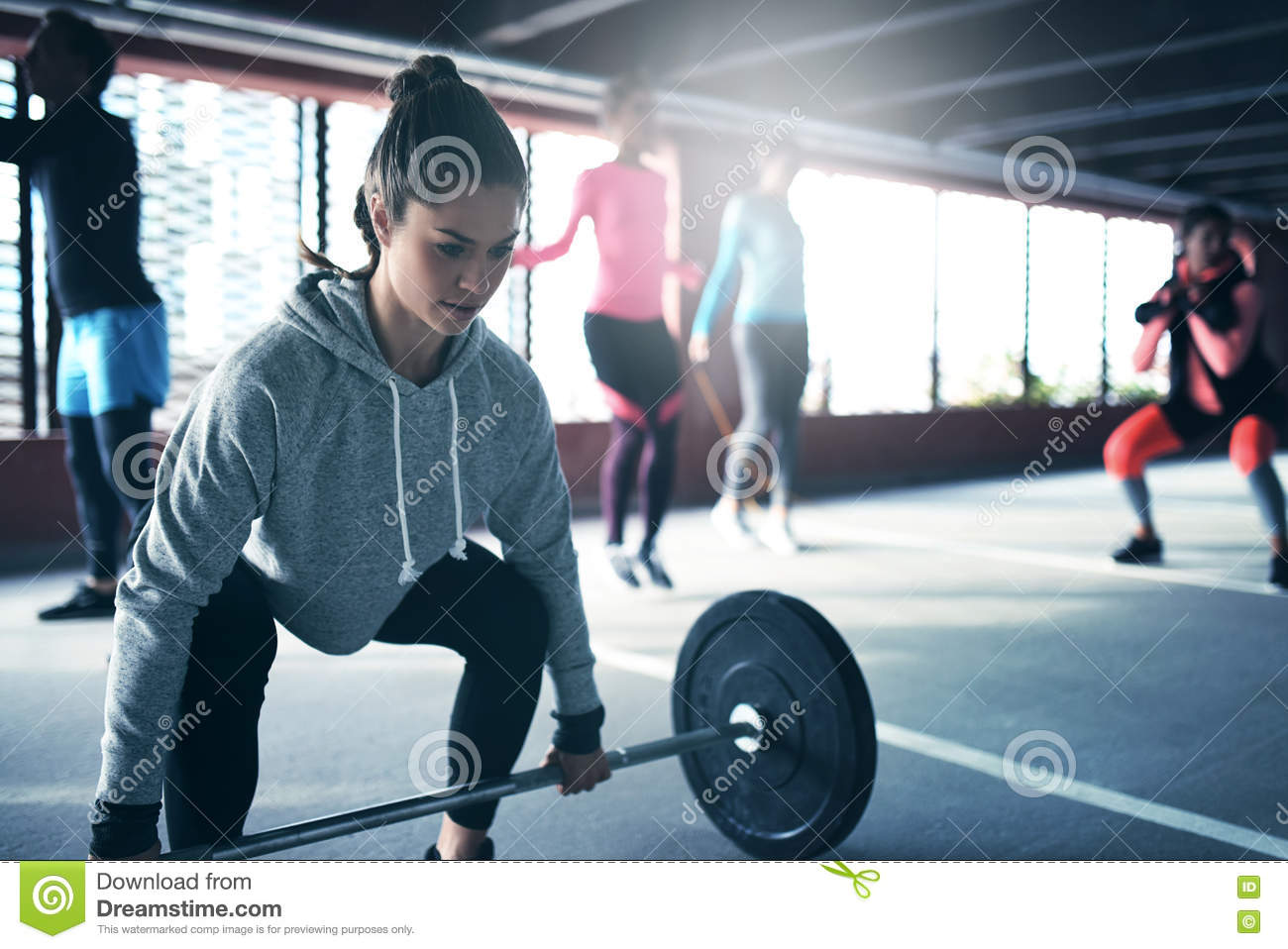 Fit healthy woman lifting a weight barbell