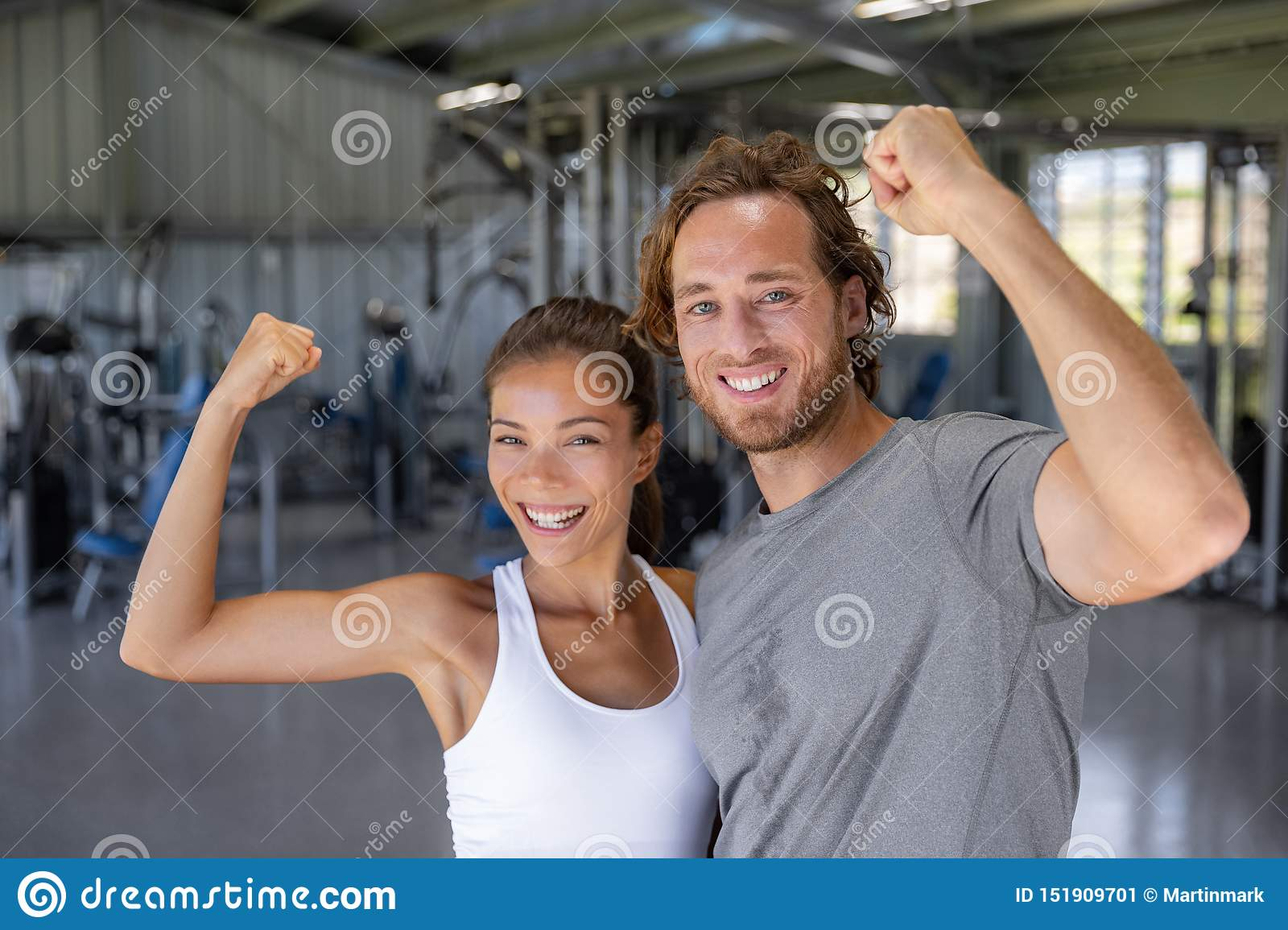 Fit power couple happy flexing strong arms showing off success training at fitness gym - Smiling Asian woman