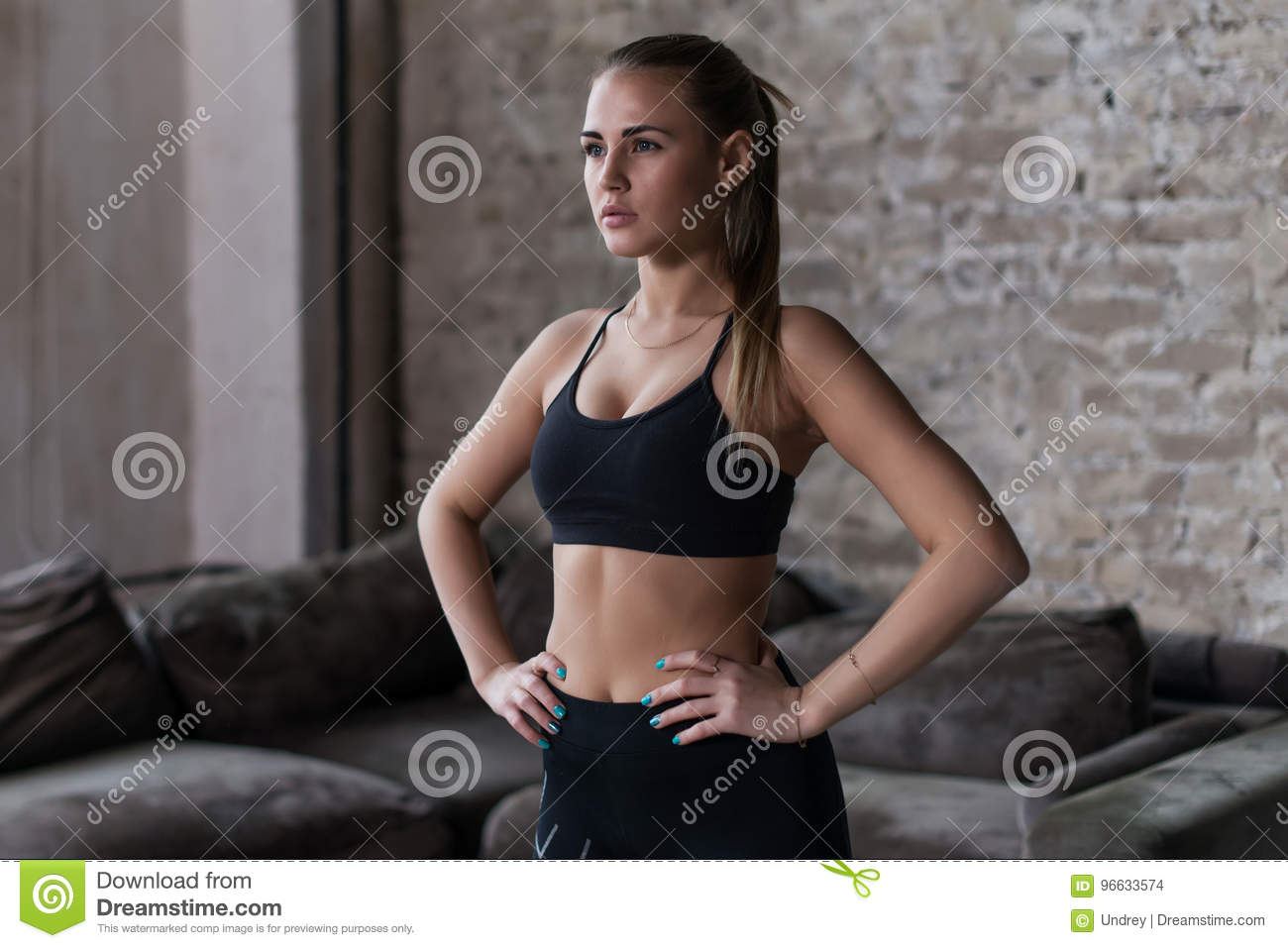 Fit female model in black sportswear with pony tail posing in loft interior looking away from camera