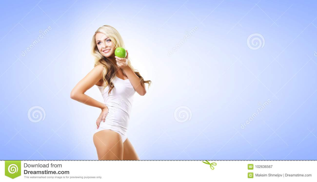 Fit and sporty girl in white underwear. Beautiful and healthy woman eating green apple over blue background. Sport, fitness, diet