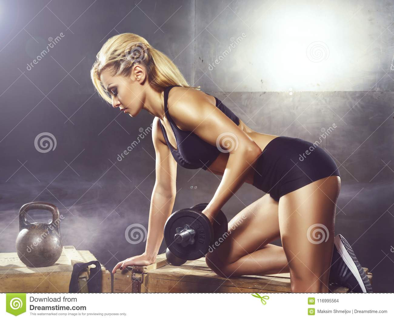 Fit and sporty young girl having a training. Underground gym. Health, sport, fitness concept.