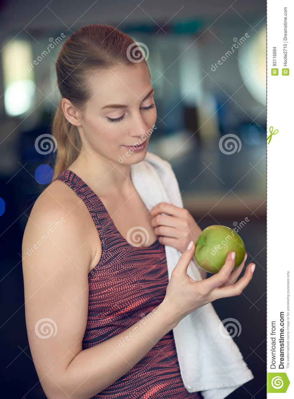Fit sporty young woman contemplating a fresh green apple