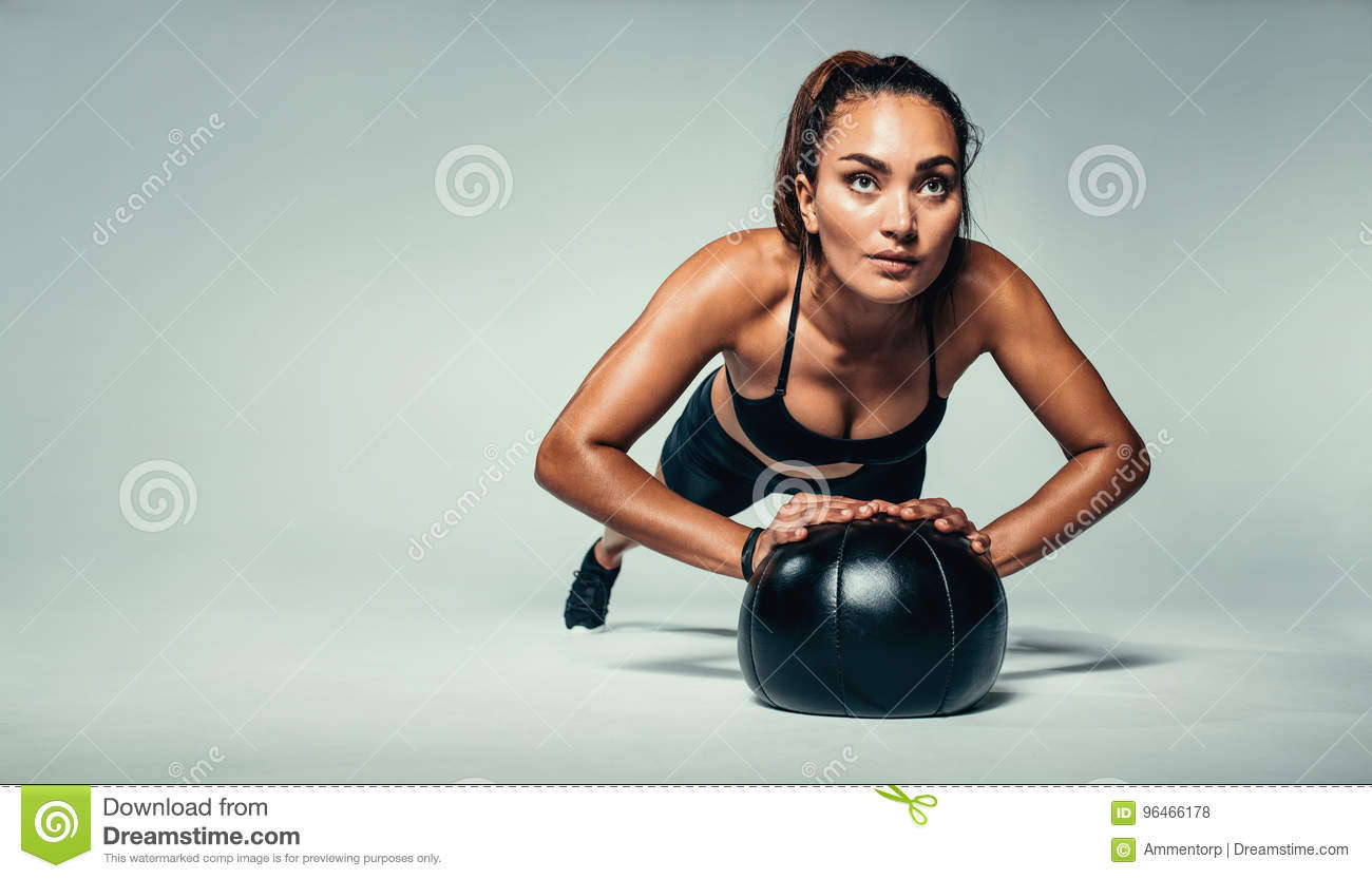 7706d947 Horizontal shot of young fit woman doing push up on medicine ball. Fitness  female exercising with a medicine ball on grey background.