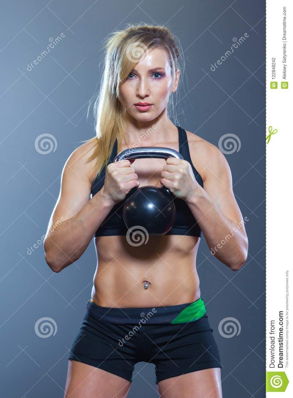 Fit woman doing squats with kettlebell in sport club. gym