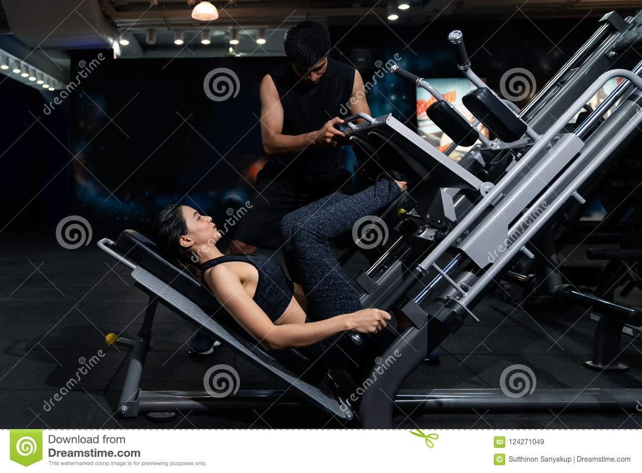 Fit woman working out with trainer at the gym, Woman doing muscle training at the gym. Athlete working out at the gym by pulling w