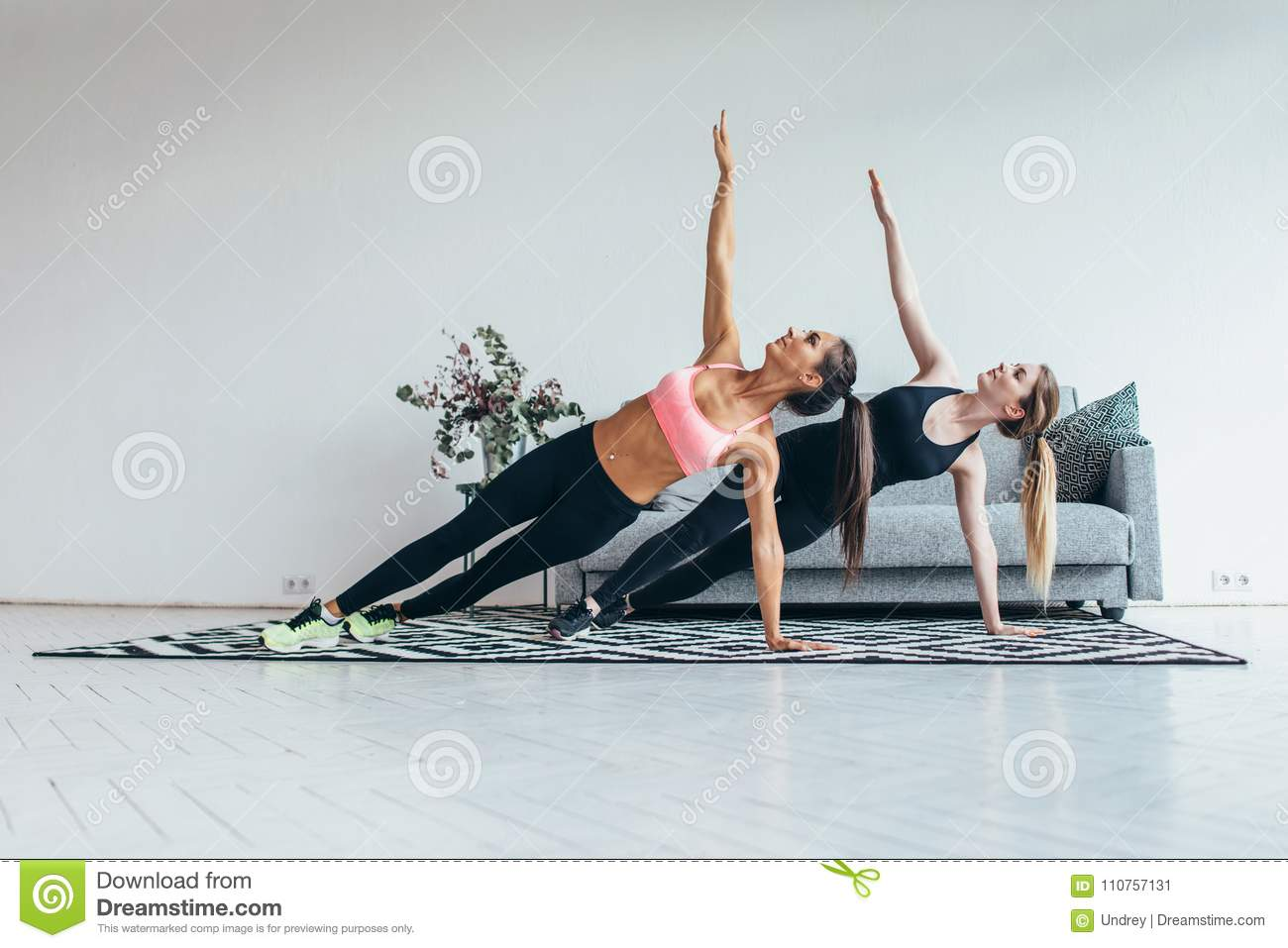 Fit women doing side plank exercise practicing pilates at home