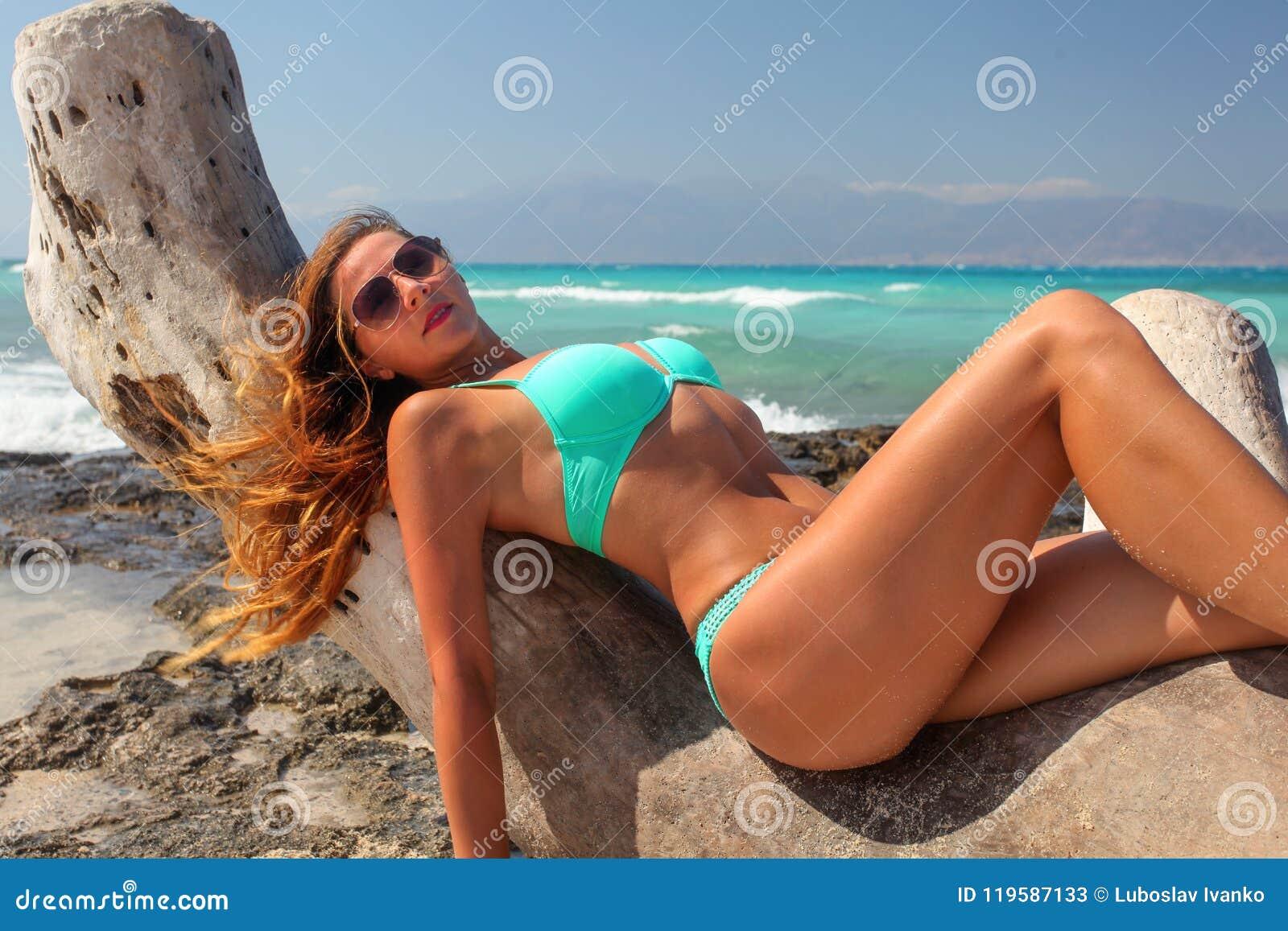Fit young woman in cyan blue bikini swimwear, wind in her hair,