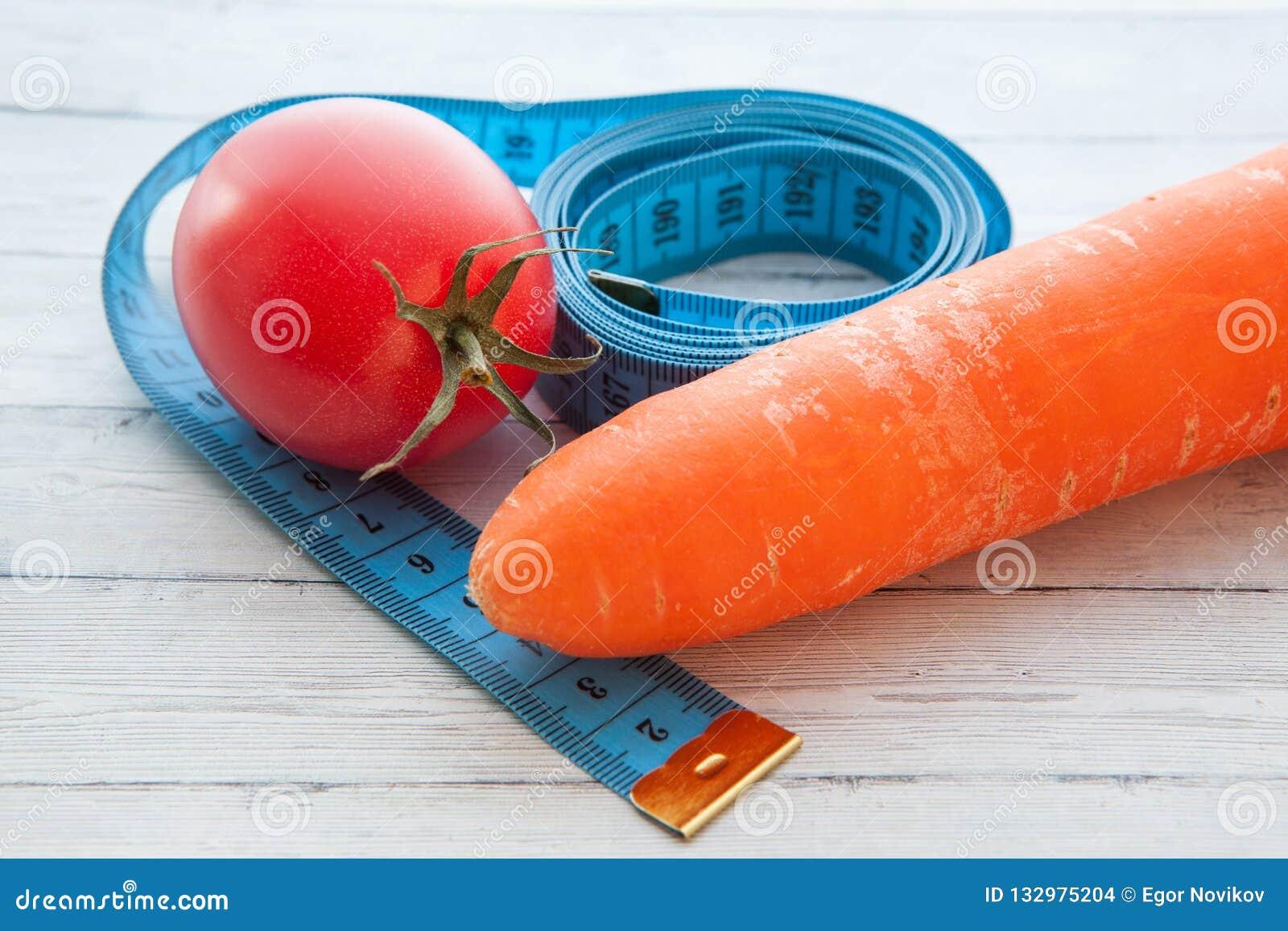Fita de medição, tomate e cenoura suculenta, o conceito de comer saudável e peso perdedor