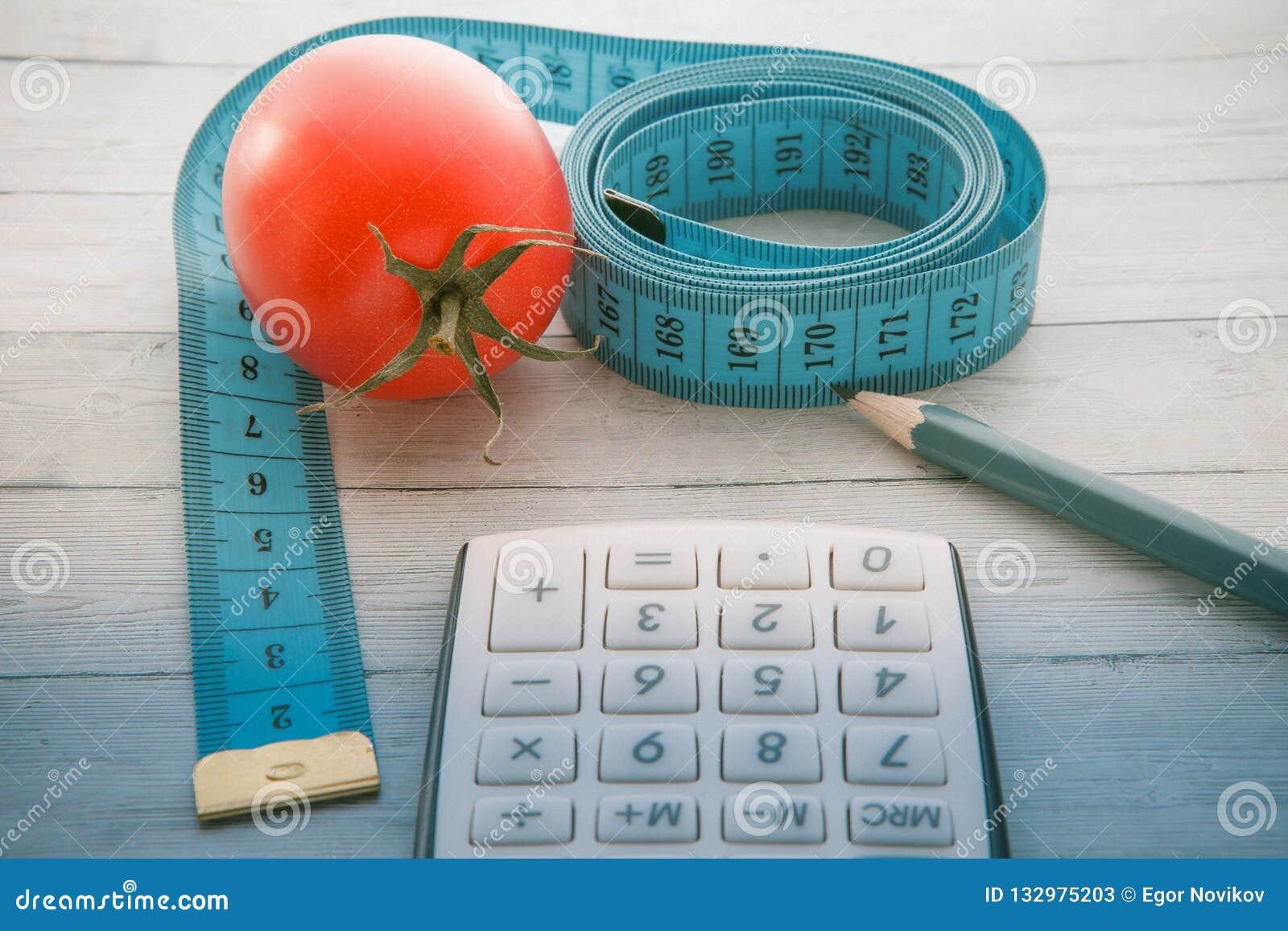 Fita e calculadora de medição com tomate suculento, conceito de comer saudável e emagrecimento, close-up