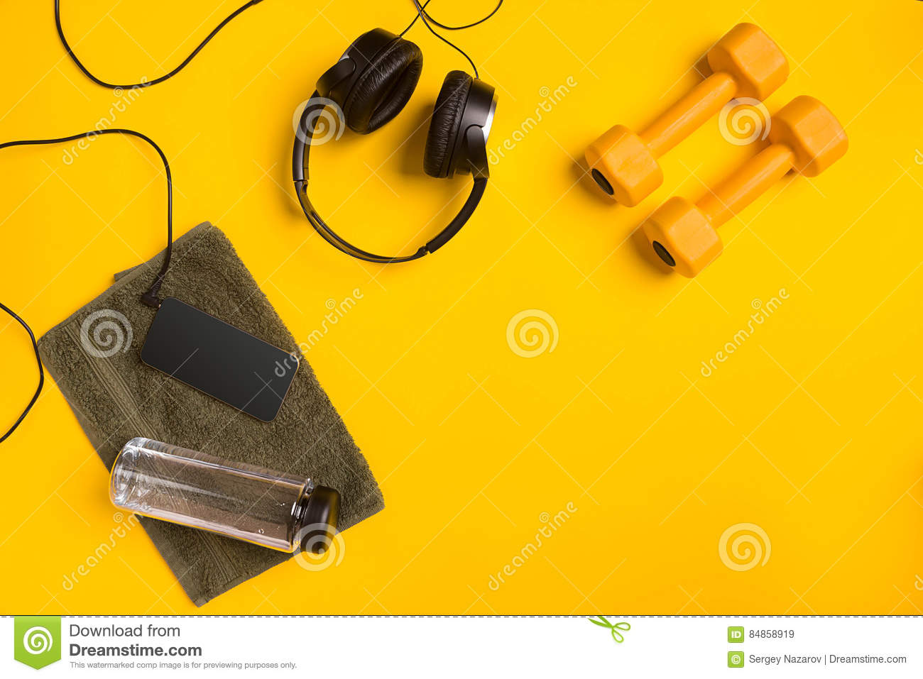 Fitness accessories on a yellow background. Dumbbells, bottle of water, towel and headphones.