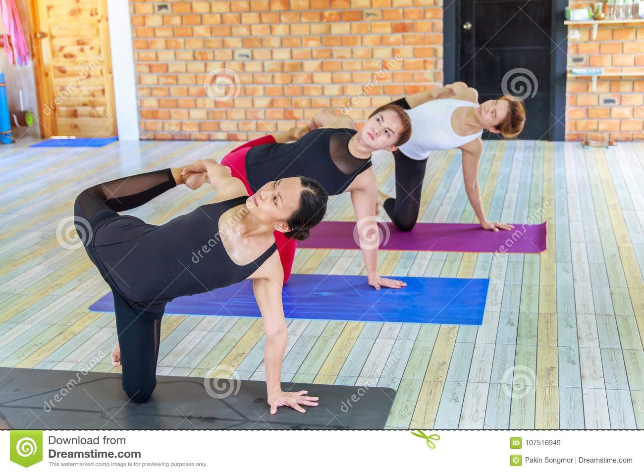 Fitness Asian Female Group Doing Namaste Yoga Pose In Row At The