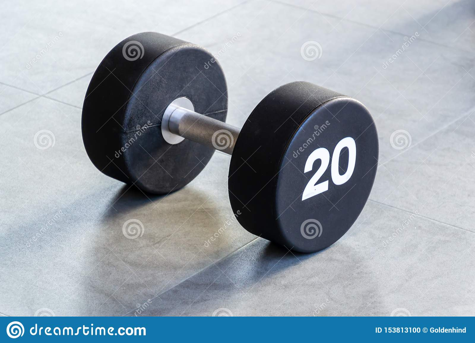 Fitness or bodybuilding concept background. Black iron dumbbell on the floor in the gym