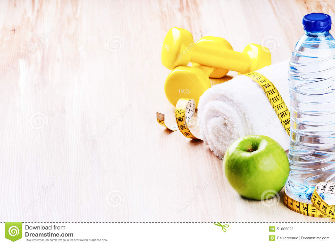 Fitness concept with dumbbells green apple and water