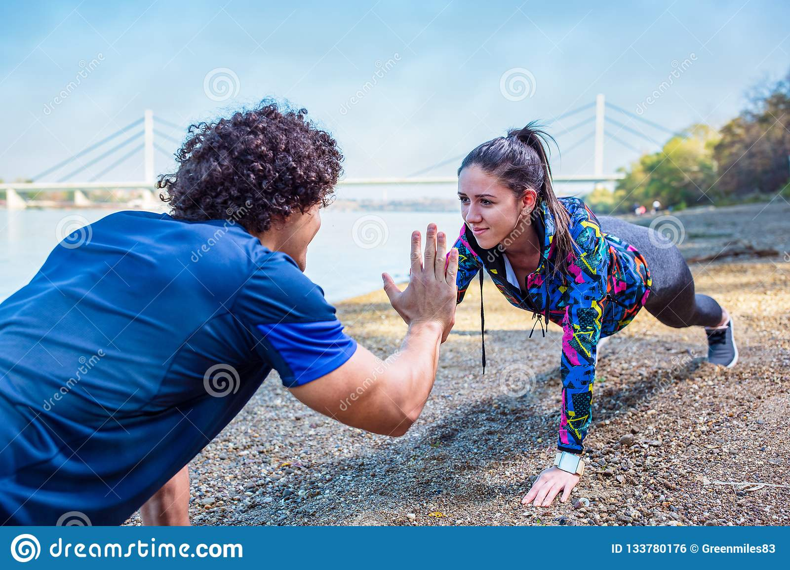 Fitness couple giving high five to each other while doing push u
