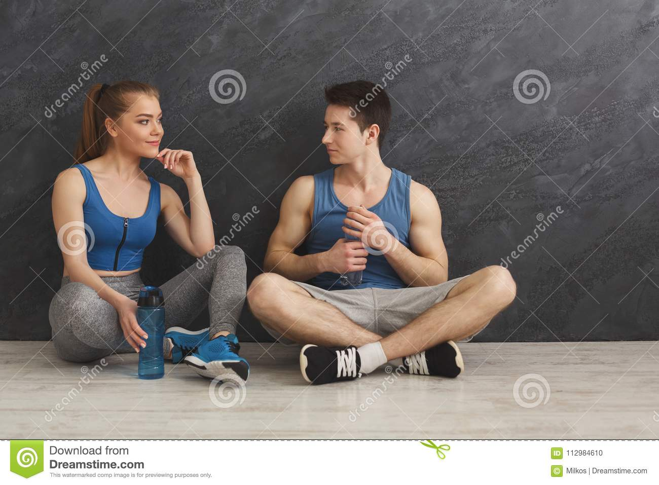 Fitness couple drinking water at gym