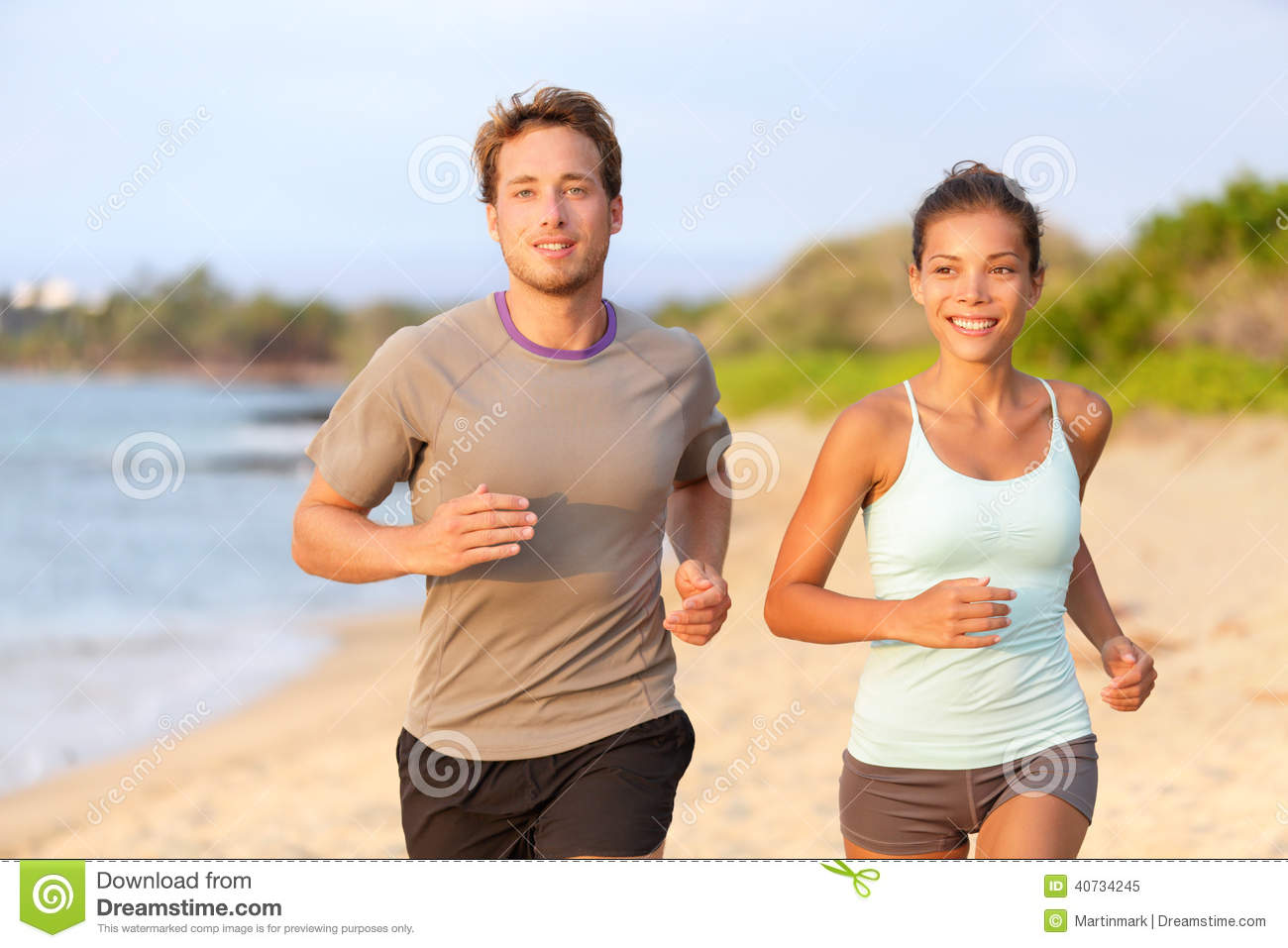 Fitness couple jogging outside on beach smiling