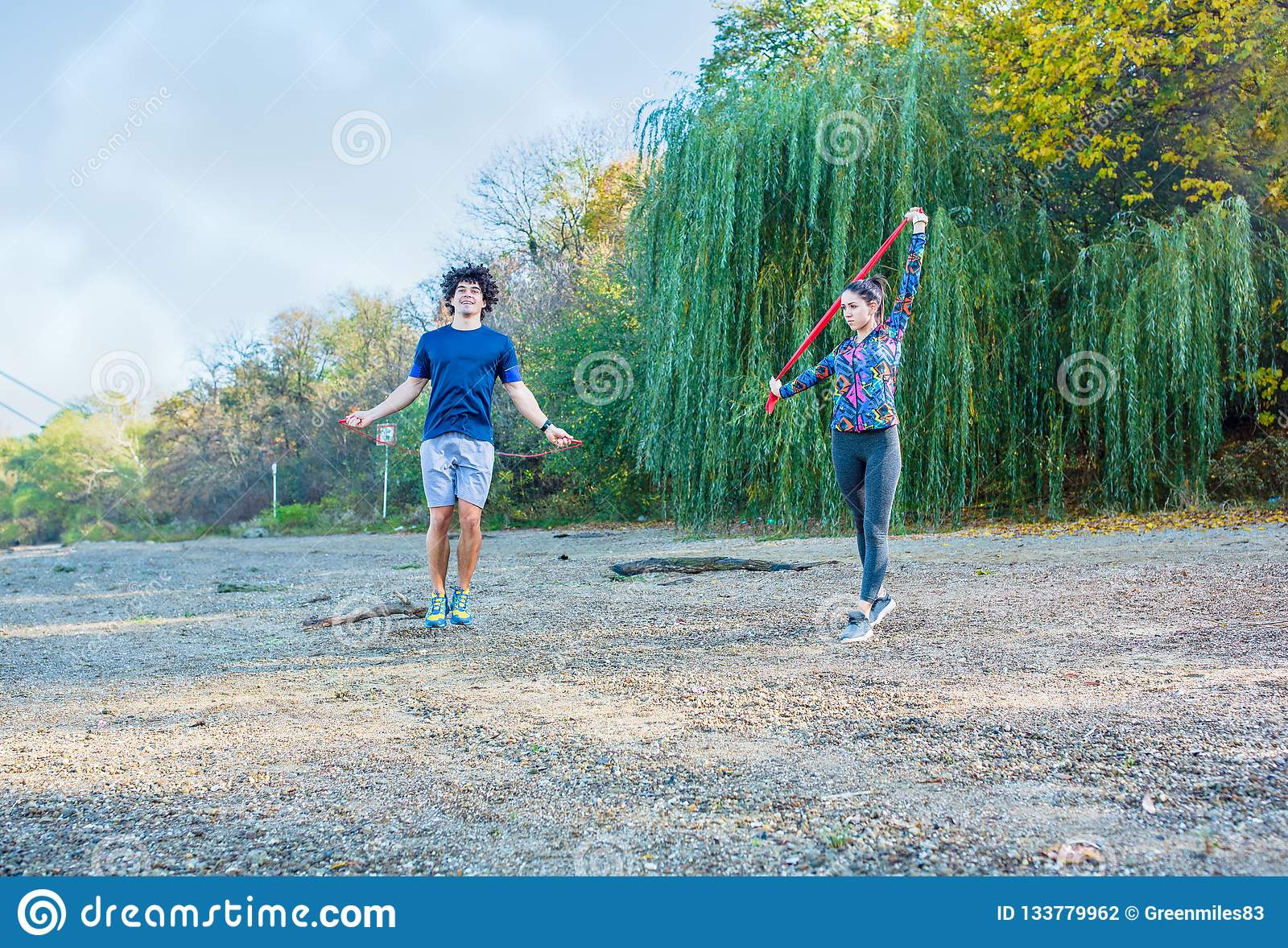 fitness couple training outdoors -Woman working out with resistance bands.