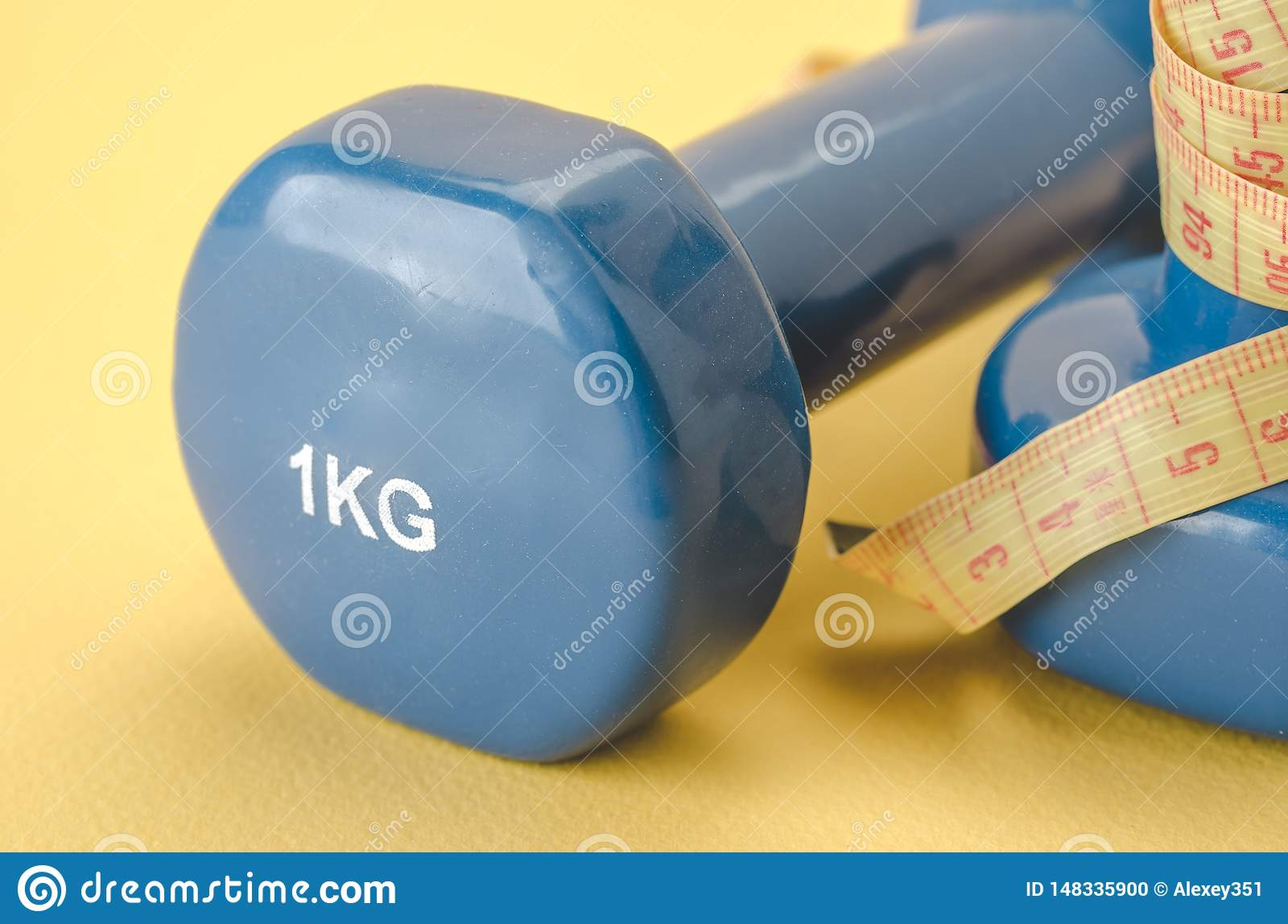 Fitness equipment with blue dumbbells with yellow centimeter/blue dumbbells with centimeter on a yellow background. Close up