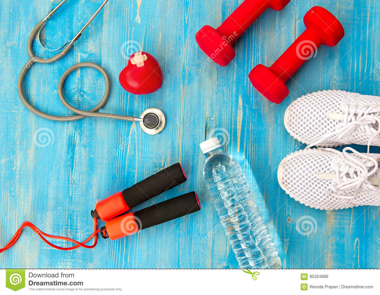 Fitness equipment gym workout and fresh water with heart and medical stethoscope on the blue background.