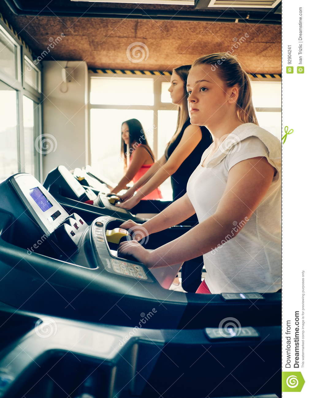 Fitness girl burning calories on the treadmill. Beautiful young cheerful girl in sportswear exercising on treadmill at gym.