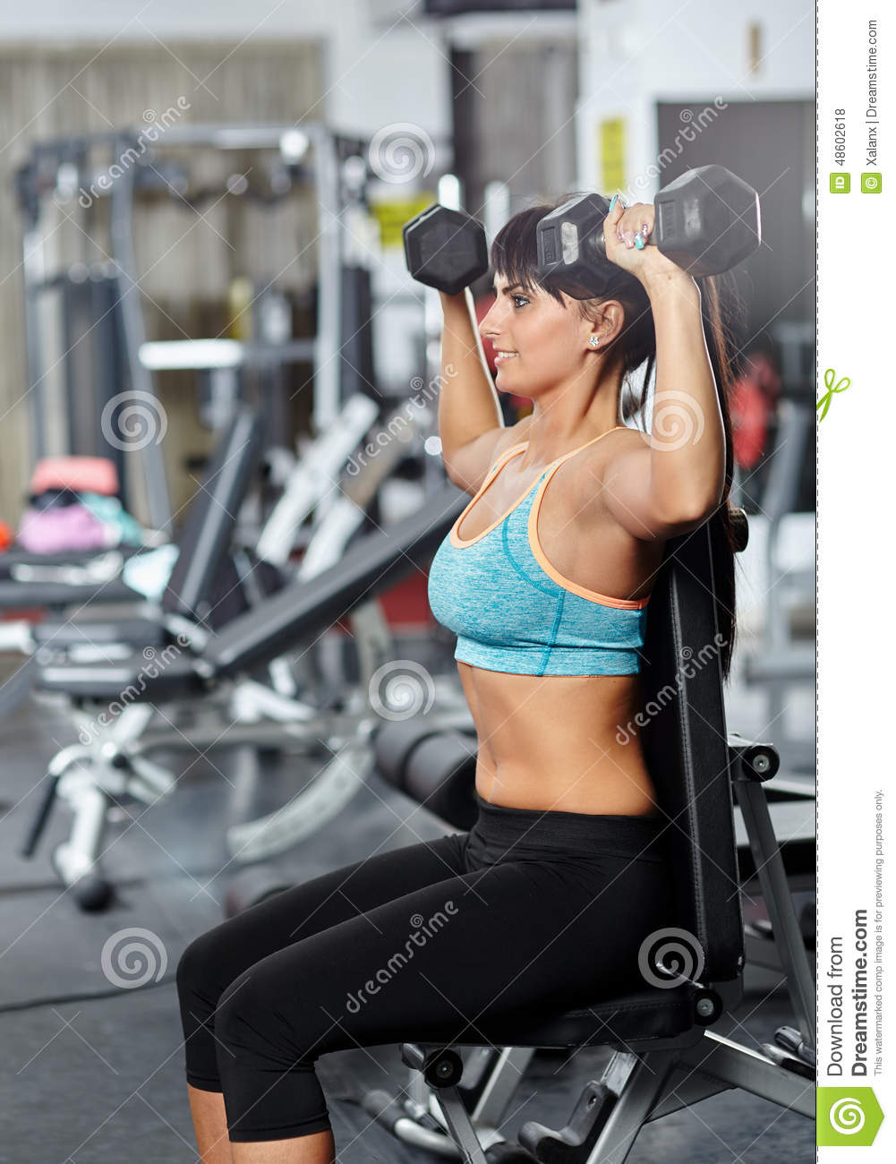 ... woman doing shoulders and triceps workout in a gym, with dumbbells