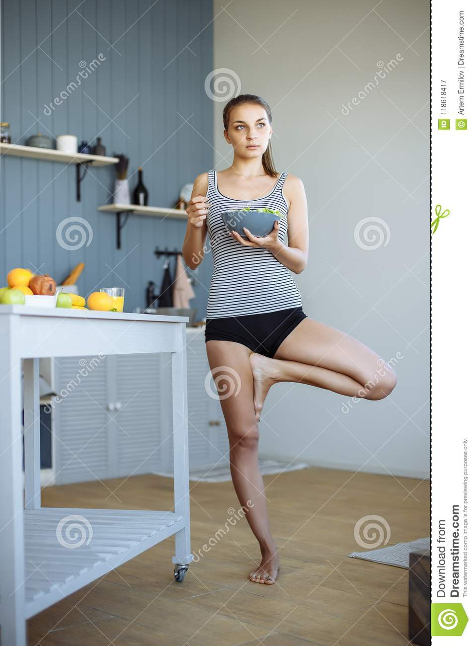 Fitness Girl Eating Healthy Food And Doing Stretching In The Kitchen ...
