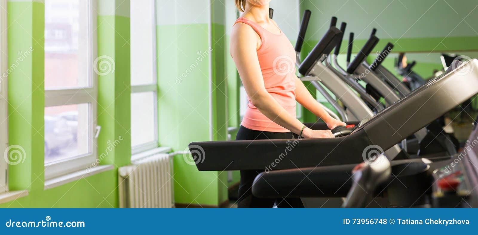 Fitness girl running on treadmill.