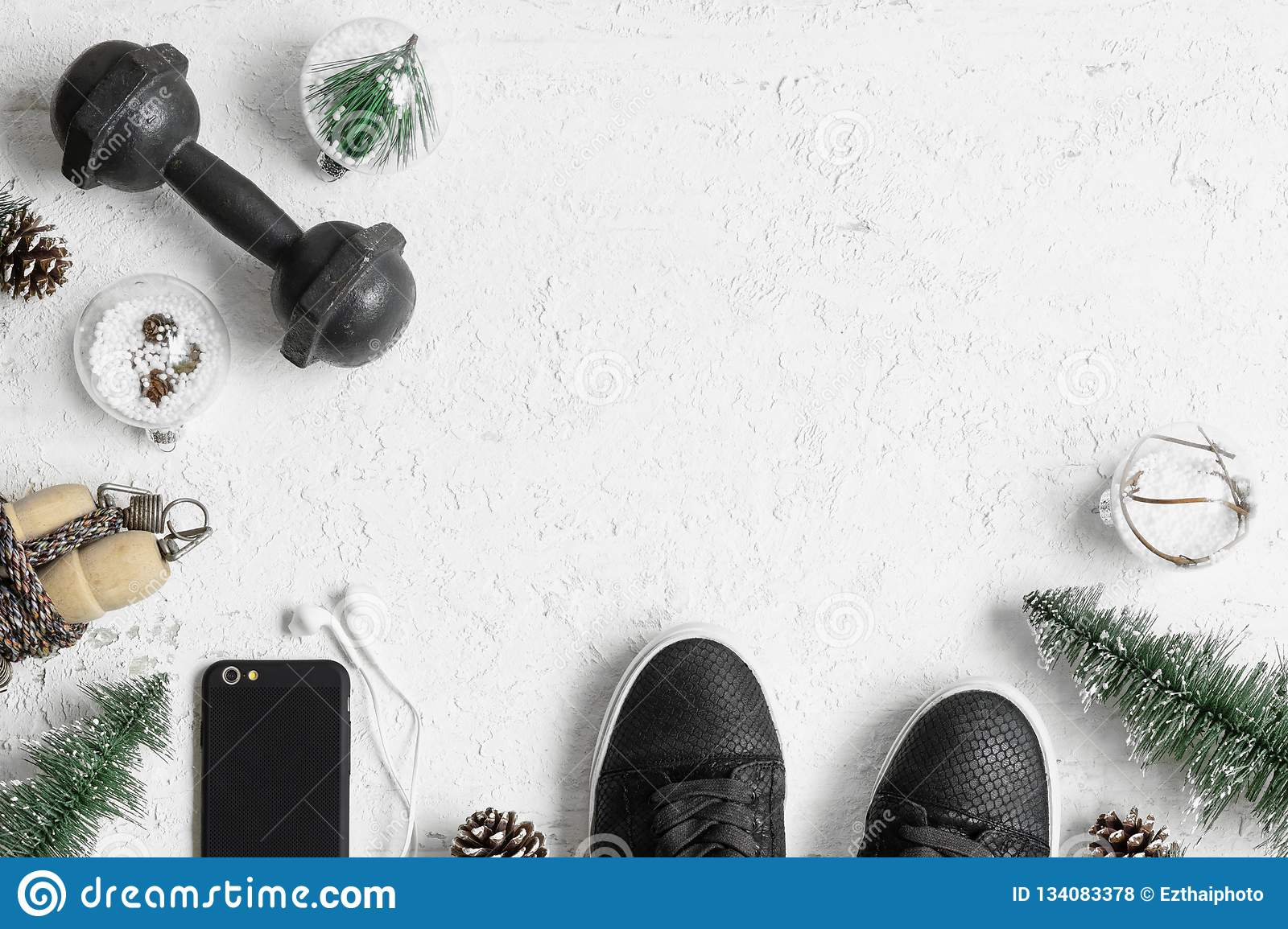 Fitness and Healthy Christmas sport composition. Overhead shot of sport shoes, dumbbells, skipping rope and Christmas ornaments