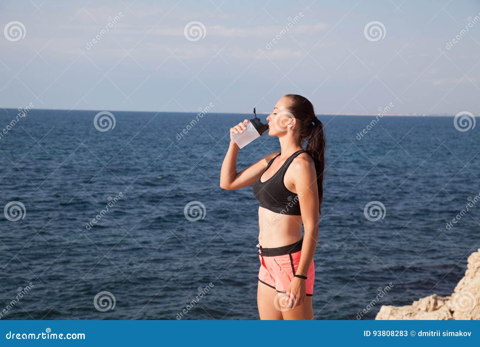 Fitness het meisje drinkt watersport opleiding