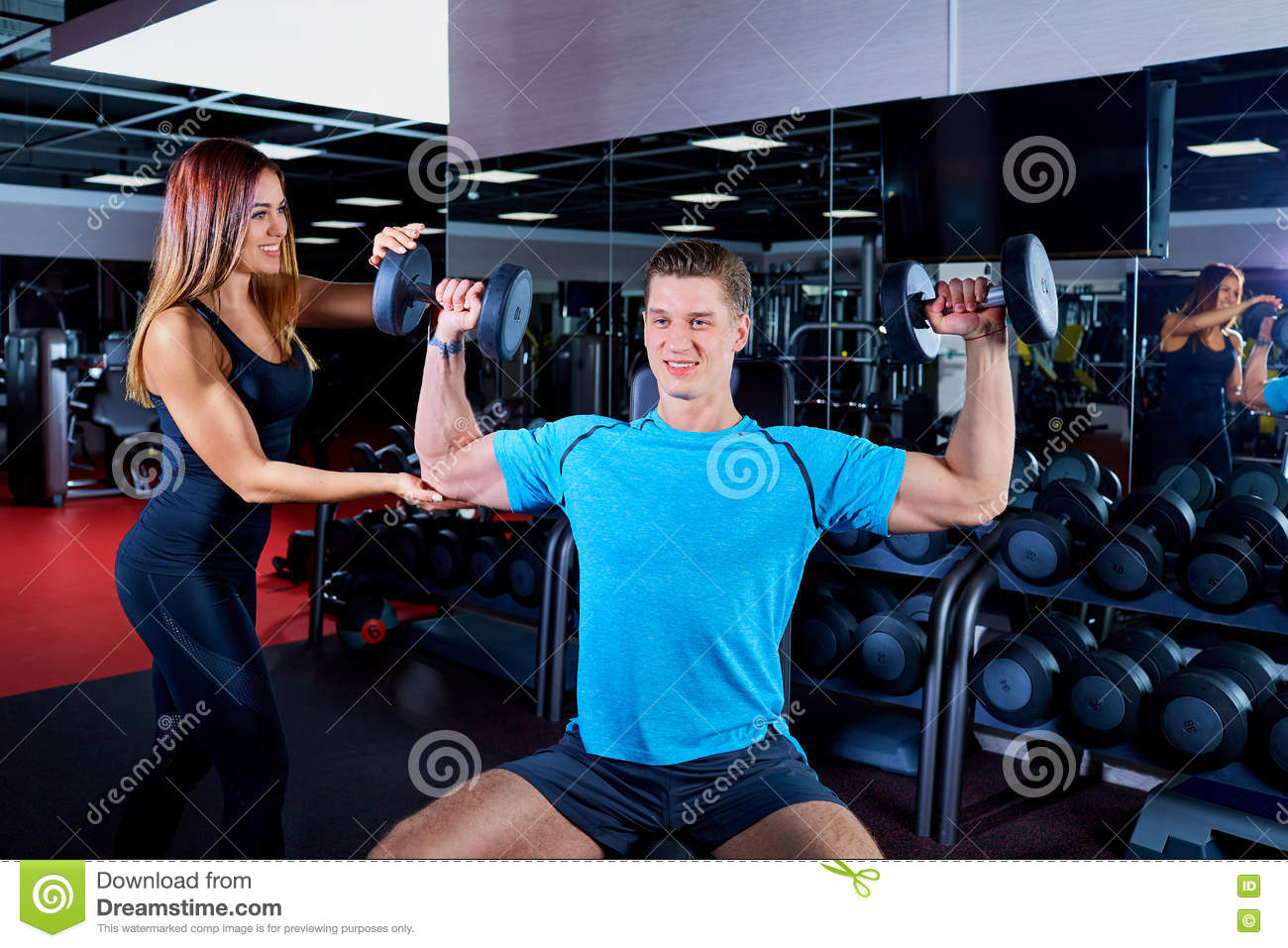 Fitness instructor woman exercising with his client at the gym.