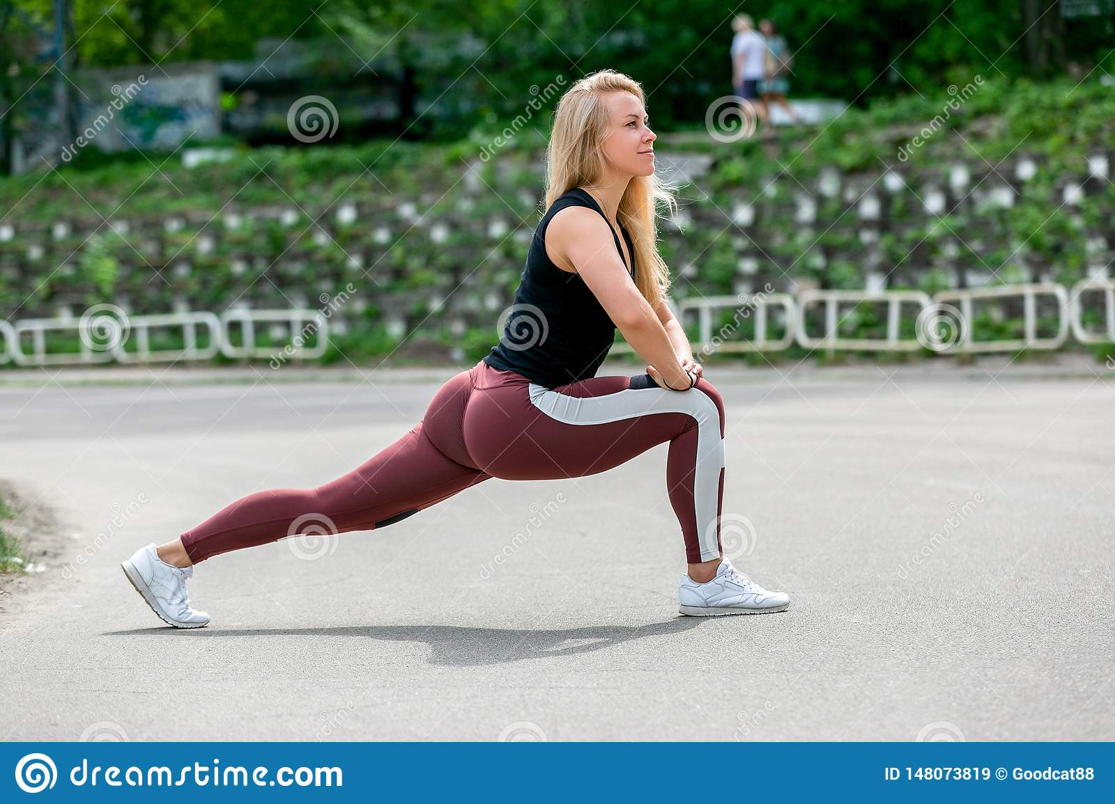 Fitness lifestyle. Young woman doing lunges to the side. Workout at the stadium. Healthy life concept. Horizontal photo