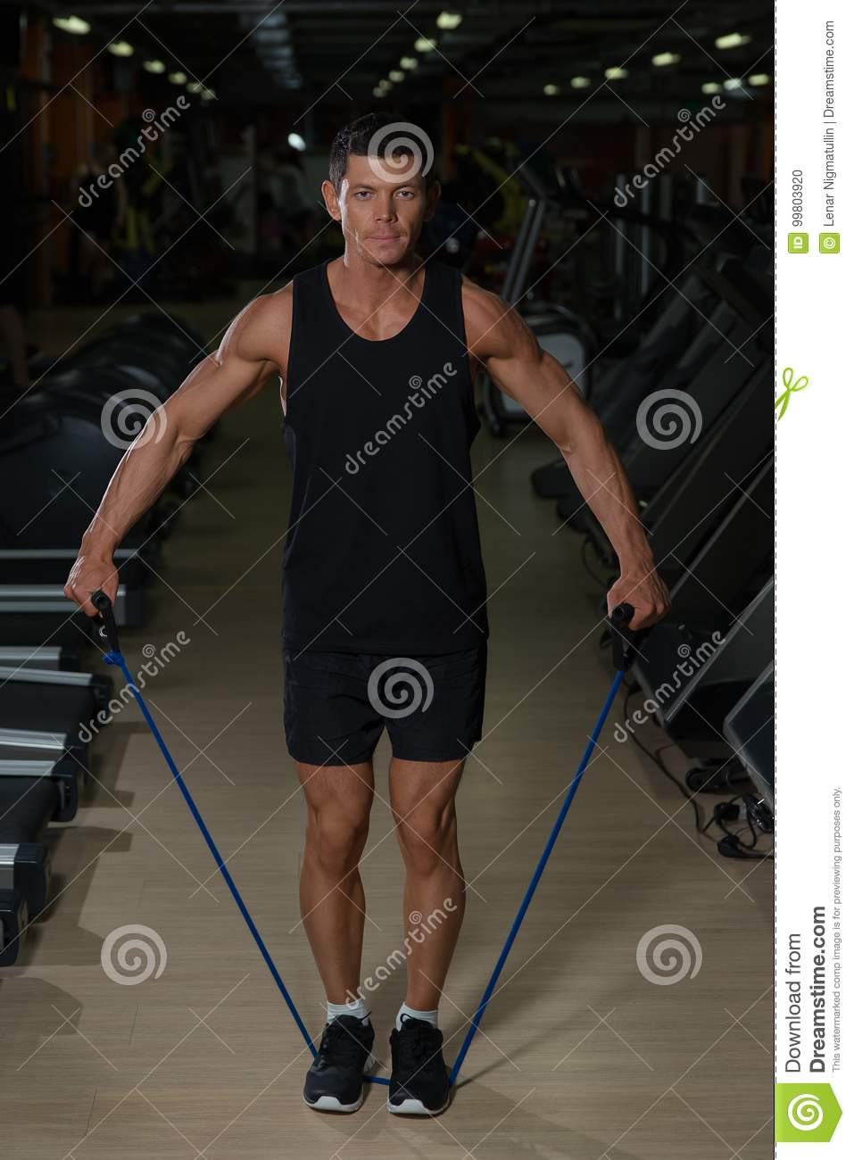 Fitness man exercising with stretching band in the gym. Muscular sports man exercising with elastic rubber band.