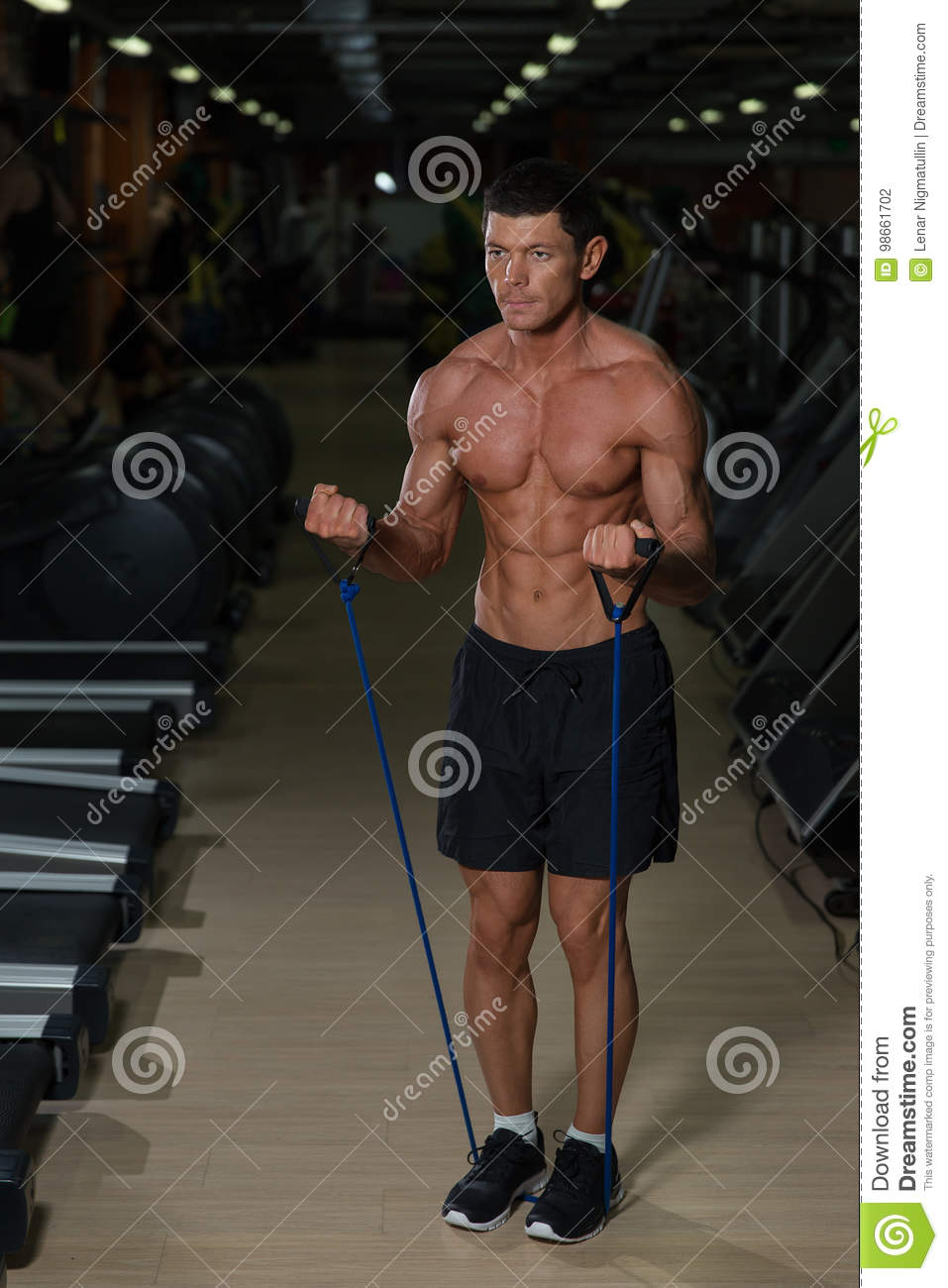 Fitness man exercising with stretching band in the gym. Muscular sports man exercising with elastic rubber band. Guy working out w