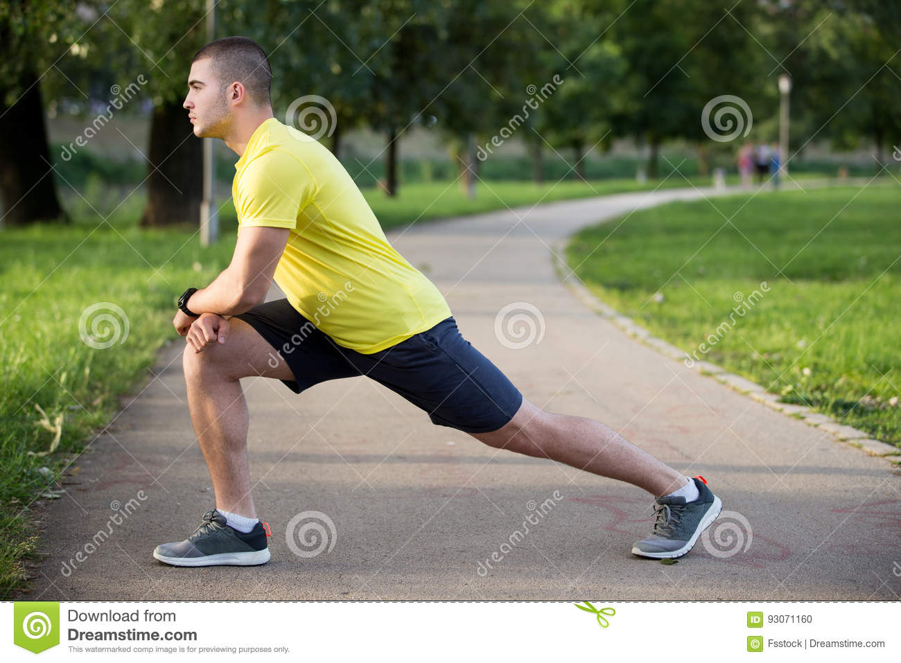 Fitness man stretching arm shoulder before outdoor workout. Sporty male athlete in an urban park warming up.