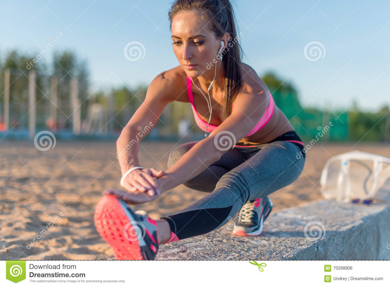 Fitness model athlete girl warm up stretching her hamstrings, leg and back. Young woman exercising with headphones