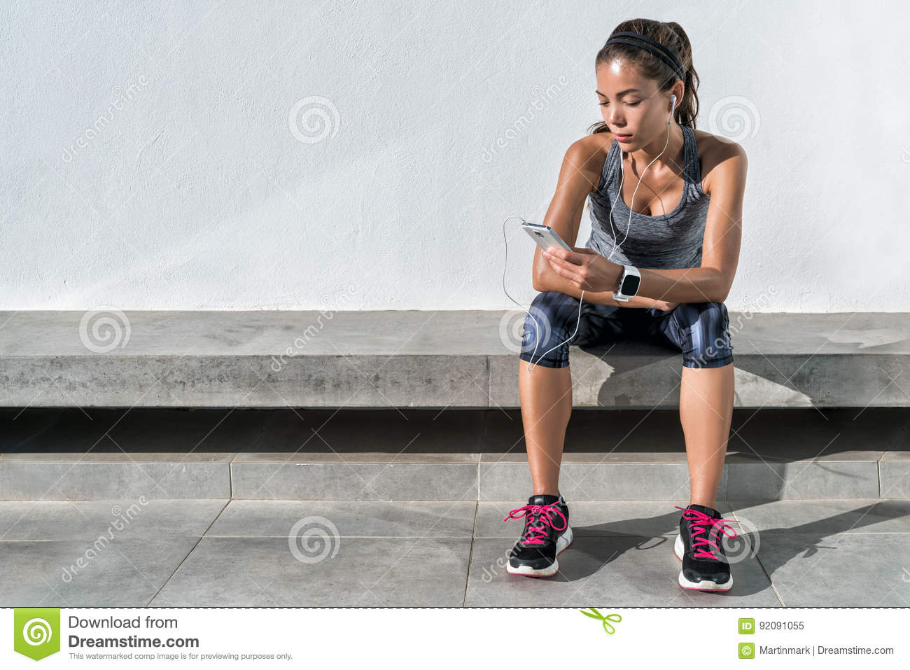 Fitness runner girl using music mobile phone app